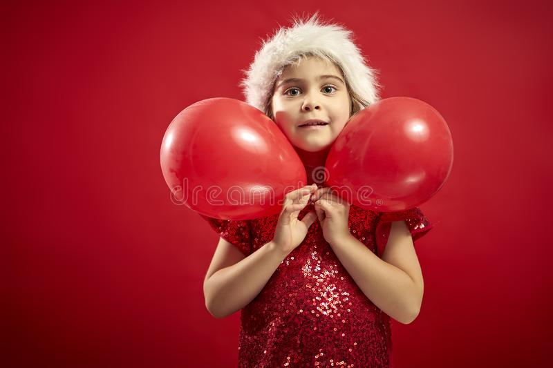 Adorable little girl in a Christmas dress in a Santa`s hat with a christmas gift stock images