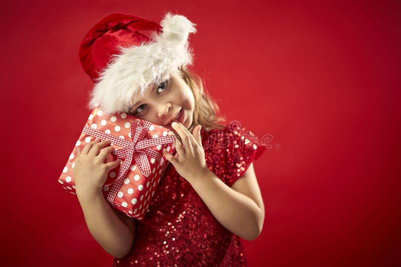 Adorable little girl in a Christmas dress in a Santa`s hat with a christmas gift royalty free stock images