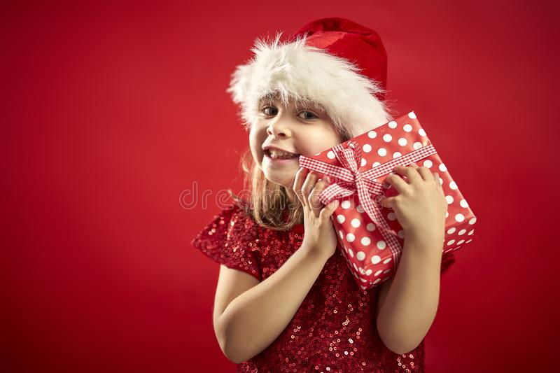 Adorable little girl in a Christmas dress in a Santa`s hat with a christmas gift stock image