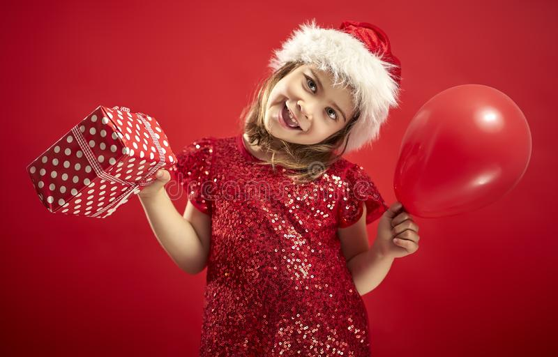 Adorable little girl in a Christmas dress in a Santa`s hat holding a present stock photos