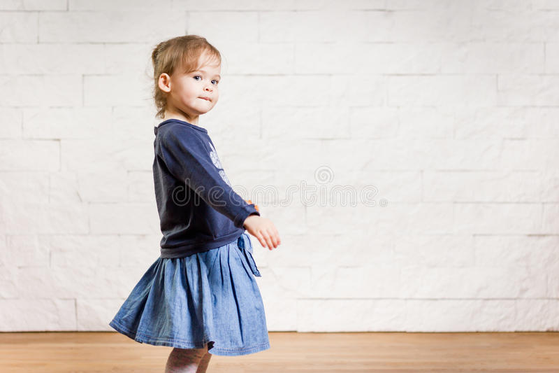 Adorable little girl dancing in the room stock image