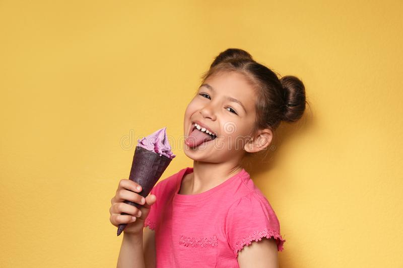 Adorable little girl with delicious ice cream. Against color background stock photography