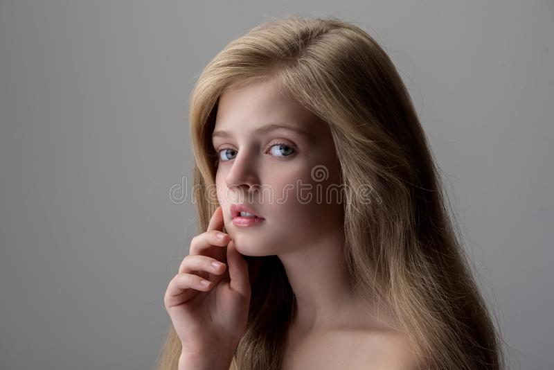 Adorable little girl is dreaming. Delightful cute female child is standing and looking at camera pensively while touching her chin. She is posing with naked stock image
