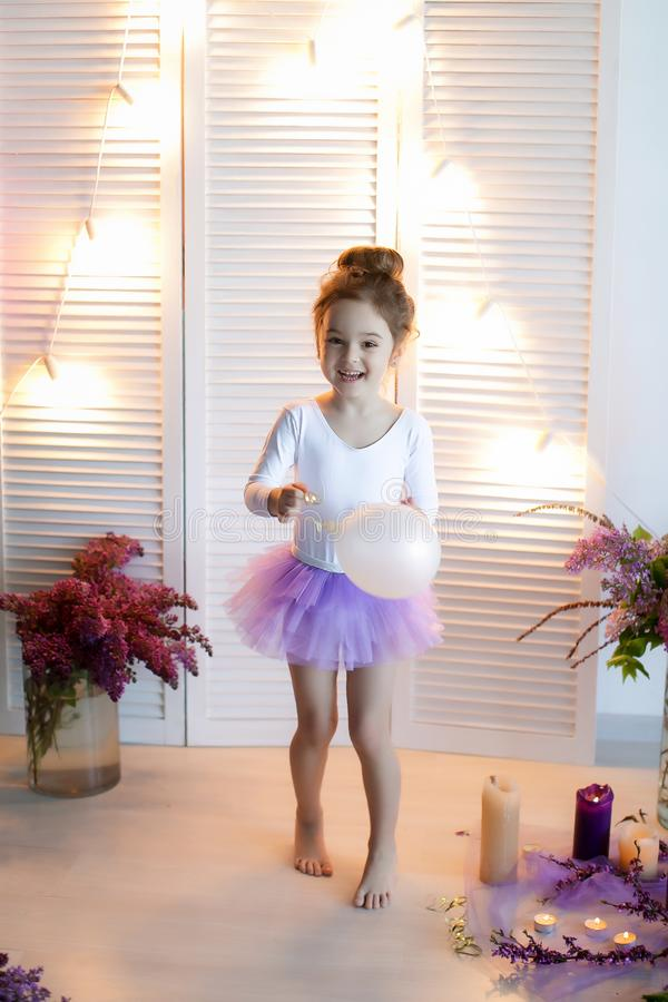 Adorable little girl dressed as a ballerina in a tutu, tying her ballet slippers. royalty free stock images