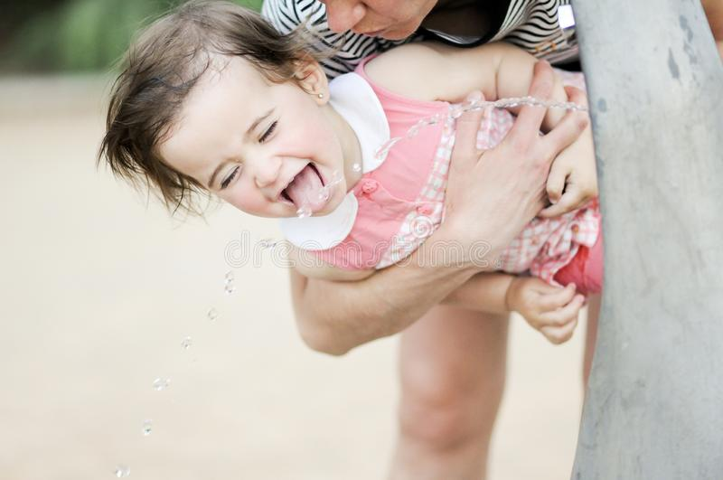 Little girl drinking water in a park fountain. Adorable little girl drinking water in a park fountain stock photography
