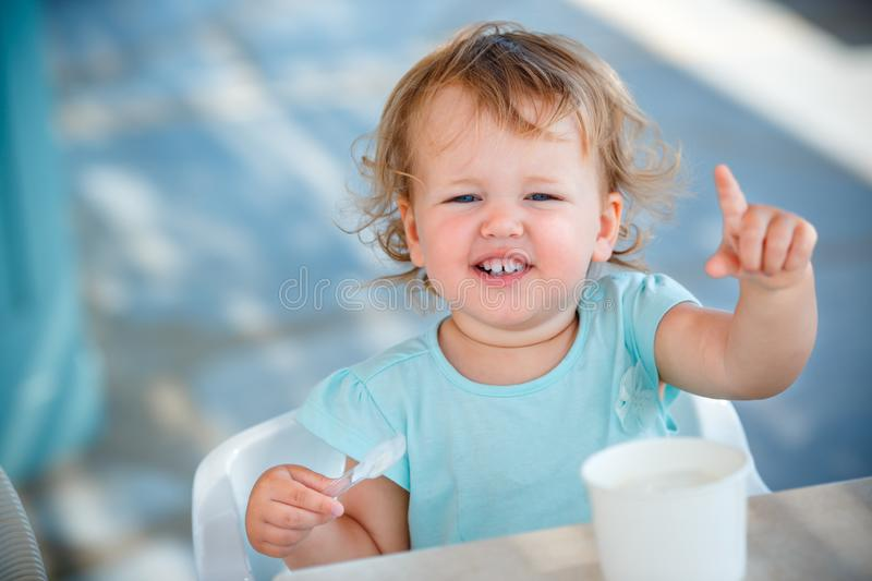 Adorable little girl eating ice cream at outdoor cafe royalty free stock image