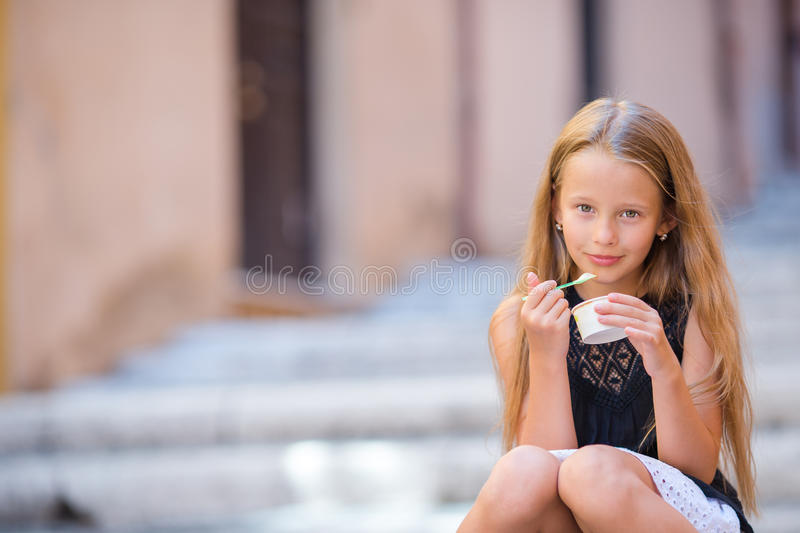 Adorable little girl eating ice-cream outdoors at summer. Cute kid enjoying real italian gelato in Rome royalty free stock photos