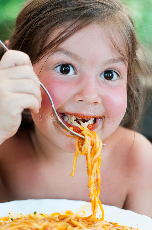 Adorable little girl eating pasta royalty free stock image