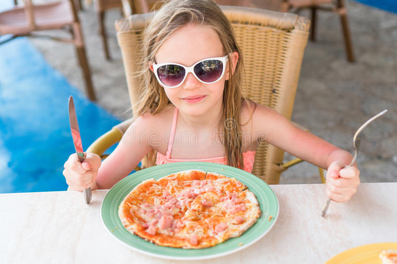 Adorable little girl eating pizza for lunch royalty free stock photography