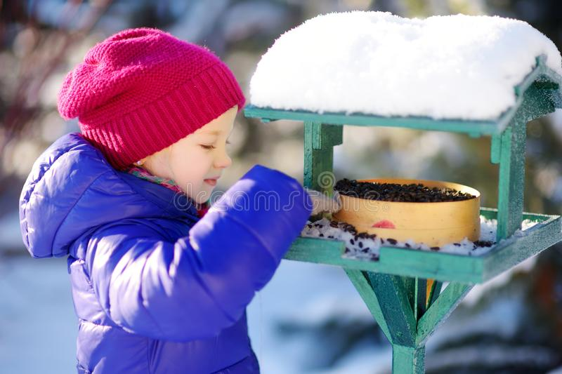 Adorable little girl feeding birds on chilly winter day in city park. Child helping birds at winter. Winter activities for kids stock images