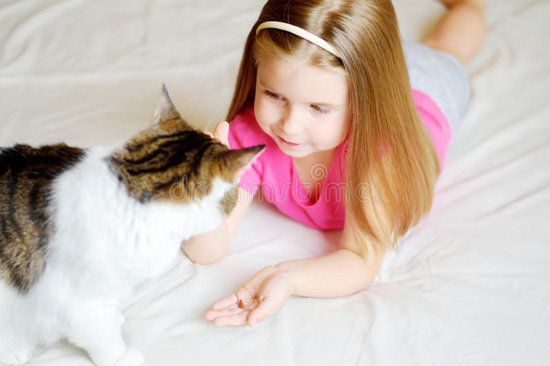 Adorable little girl feeding her cat royalty free stock image