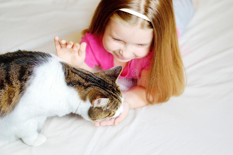 Adorable little girl feeding her cat. At home stock photography