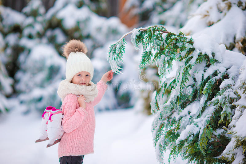 Adorable little girl going to skate in warm winter snow day outdoors. Cute little kid girl is going skate outdoors royalty free stock photo