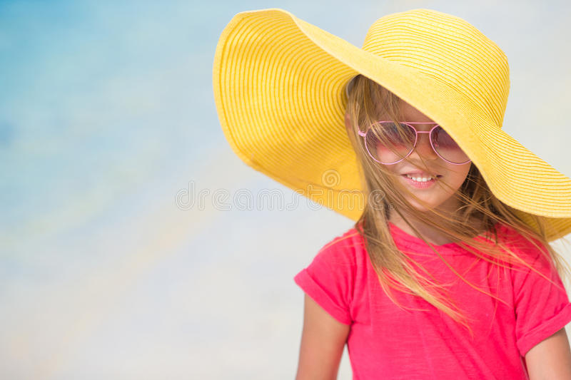 Adorable little girl in hat at beach during summer stock photography