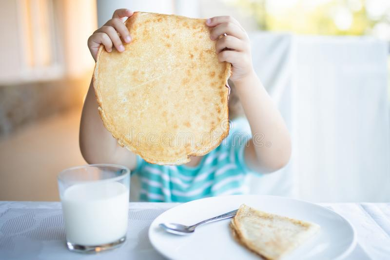 Adorable little girl having breakfast, eating pancakes and drinking milk royalty free stock photography