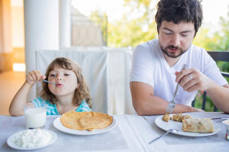Adorable little girl having breakfast with her father, eating pancakes and drinking milk stock image