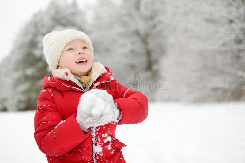 Adorable little girl having fun in beautiful winter park. Cute child playing in a snow. Winter activities for kids stock photo