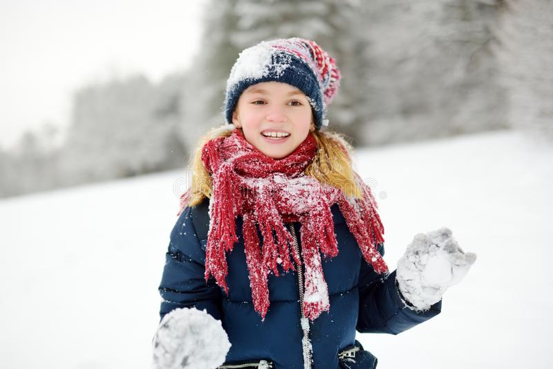 Adorable little girl having fun in beautiful winter park. Cute child playing in a snow. Winter activities for kids stock image