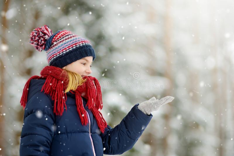 Adorable little girl having fun in beautiful winter park. Cute child playing in a snow. Winter activities for kids stock images