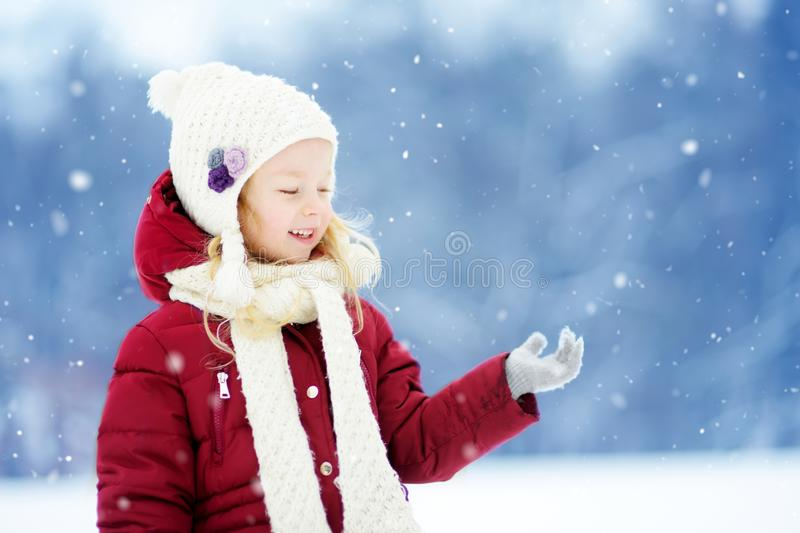 Adorable little girl having fun in beautiful winter park. Cute child playing in a snow. Winter activities for kids royalty free stock photo
