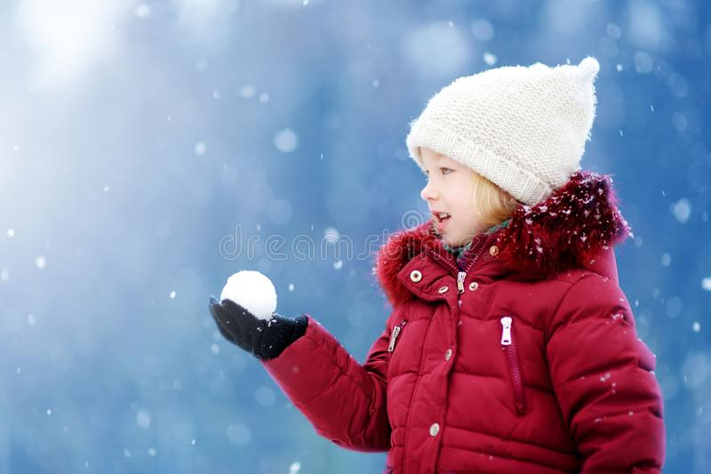 Adorable little girl having fun in beautiful winter park. Cute child playing in a snow. Winter activities for kids stock photos