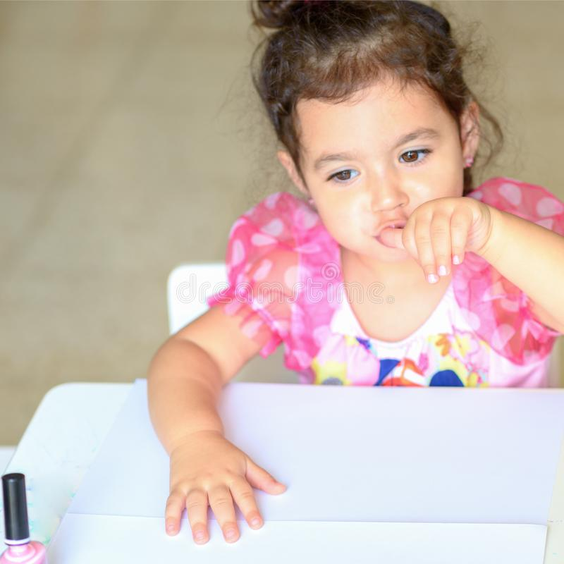 Adorable little girl having fun playing at home with colorful pink nail polish doing manicure and blowing nails. stock photos
