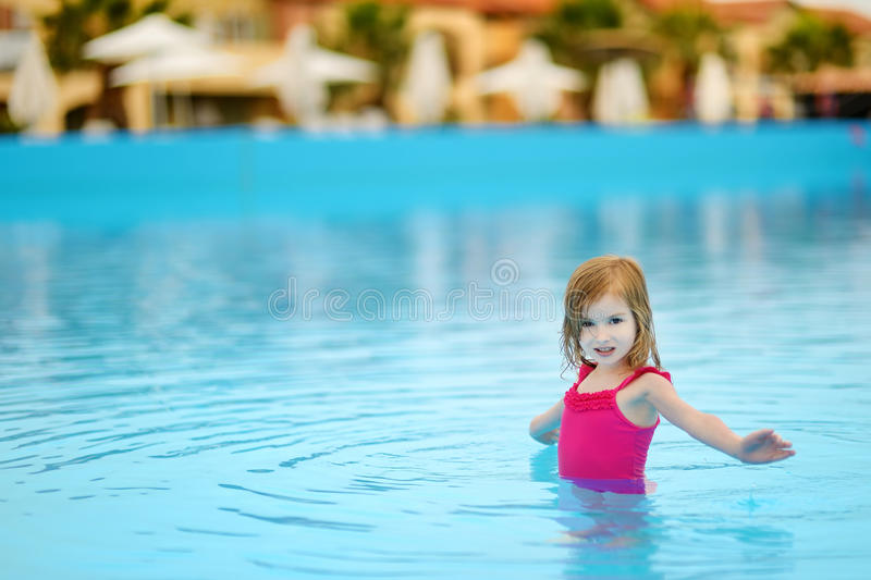 Adorable little girl having fun in a swimming pool. Cute little girl having fun in a swimming pool stock image