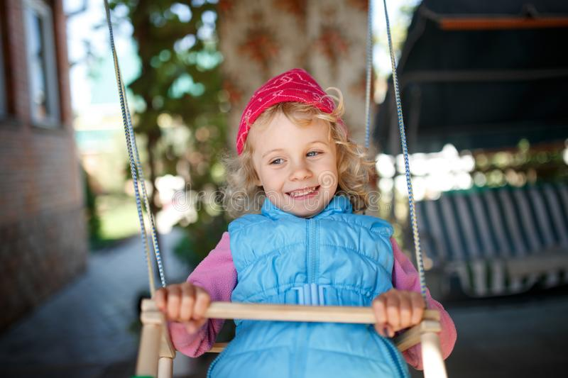 Adorable little girl having fun on a swing outdoor. royalty free stock images