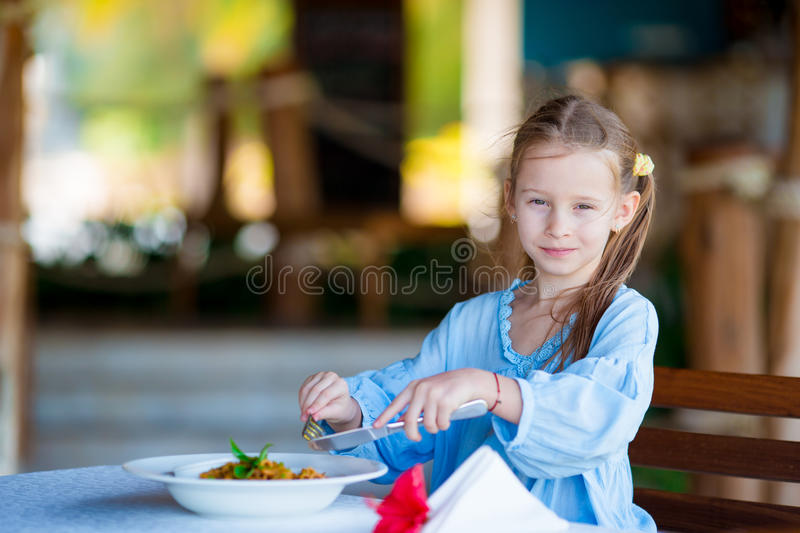 Adorable little girl having lunch at outdoor cafe. Adorable little girl having lunch at resort restaurant stock image