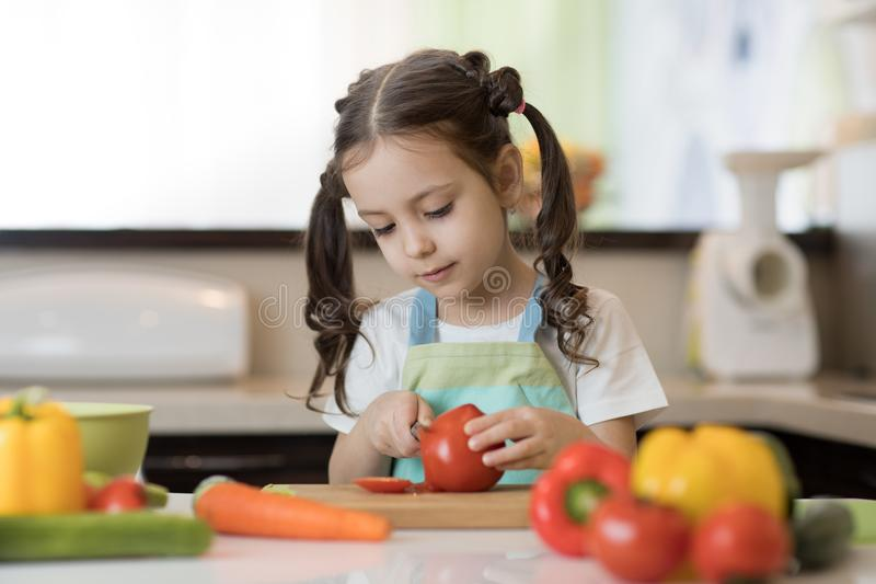 Adorable little girl helping at kitchen with salad making stock images