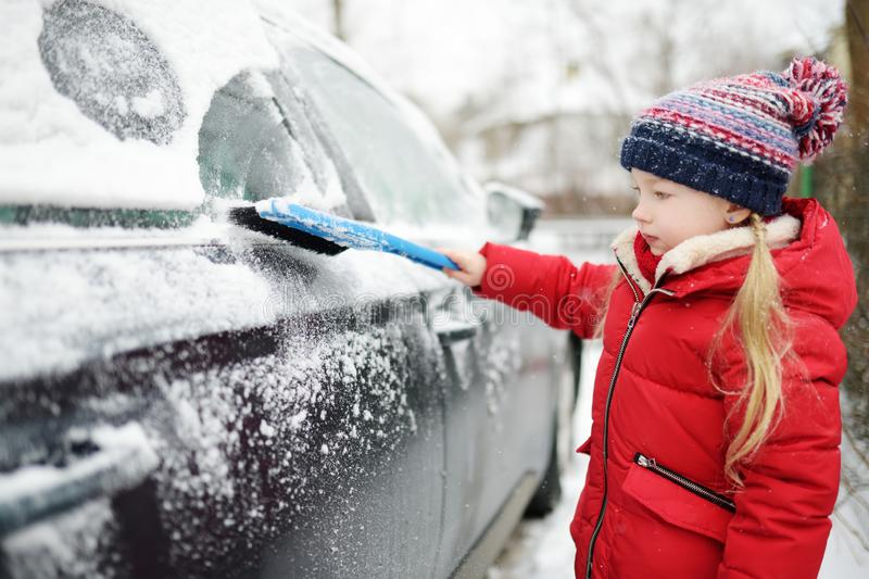 Adorable little girl helping to brush a snow from a car. Mommy`s little helper. Winter activities for kids royalty free stock image