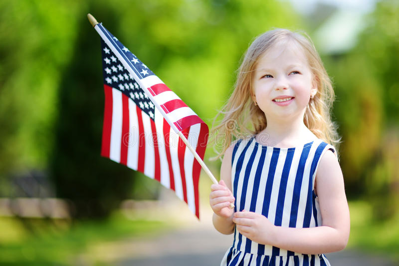 Adorable little girl holding american flag outdoors on beautiful summer day royalty free stock photos