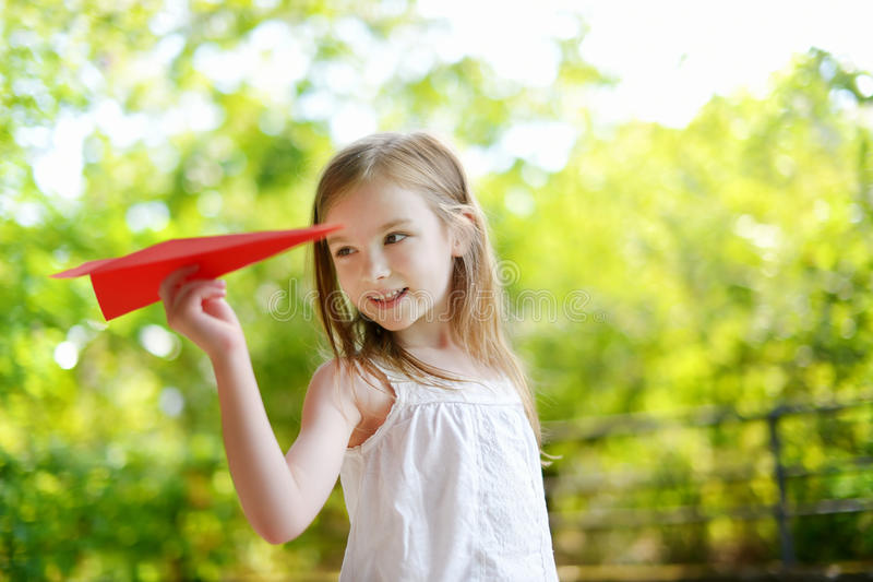 Adorable little girl holding a paper plane. Outdoors on sunny summer day stock photo