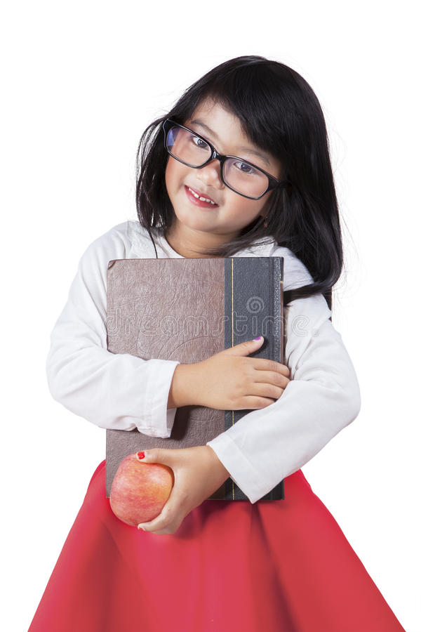 Adorable little girl holds a book and apple in studio stock image