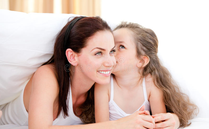 Adorable little girl kissing her mother stock photo