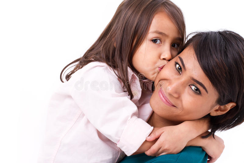 Adorable little girl kissing her mother's cheek stock photo