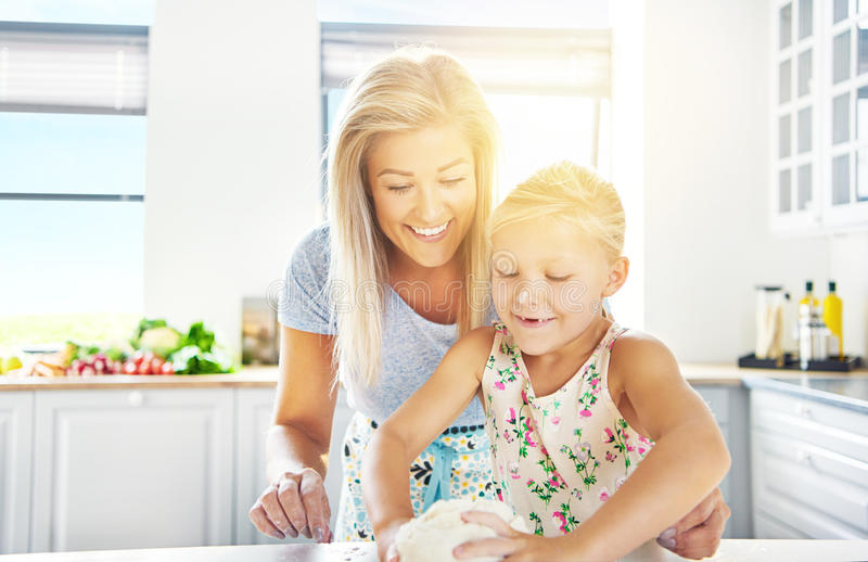 Adorable little girl kneading the dough. Watched over by her loving mother as she learns to bake, high key sun flare background royalty free stock images