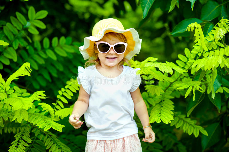 Adorable little girl laughing in a meadow - happy girl stock photos