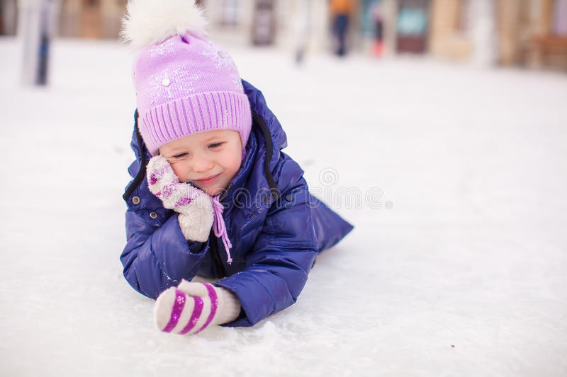 Adorable little girl laying on skating rink after. The fall. This image has attached release stock photos