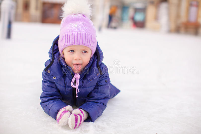 Adorable little girl laying on skating rink after. The fall. This image has attached release stock images