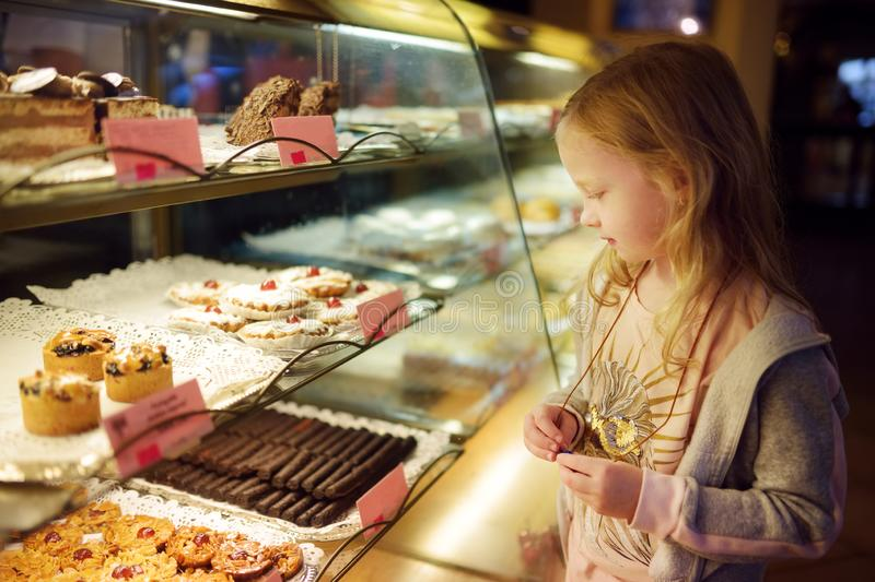 Adorable little girl looking at fresh baked cookies on display in small store in Vilnius, Lithuania. Child choosing a dessert royalty free stock photography