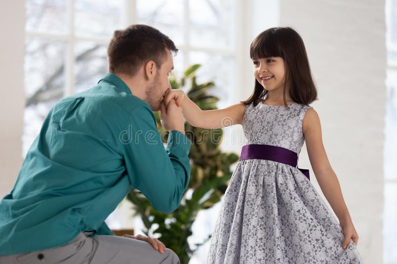 Adorable little girl making curtsey, looking at father. stock photos