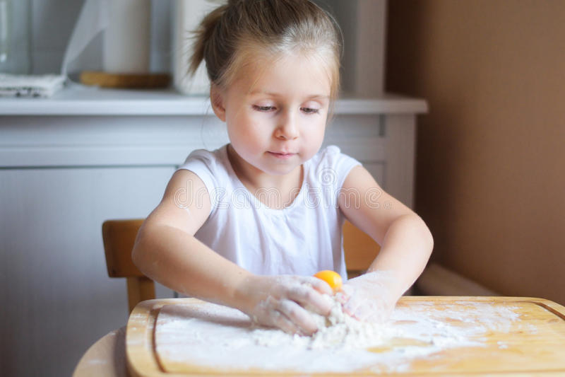 Adorable little girl making the dough for pasta. At home stock photography