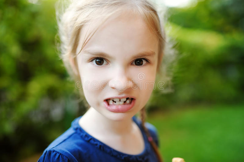 Adorable little girl making funny faces on beautiful summer day. Outdoors royalty free stock photography