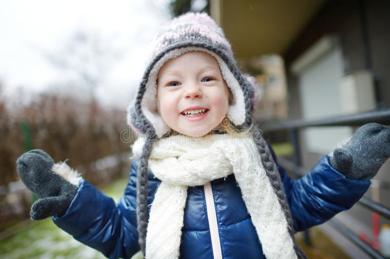 Adorable little girl making funny faces outdoors. Adorable little girl wearing winter hat making funny faces on beautiful winter day outdoors stock images
