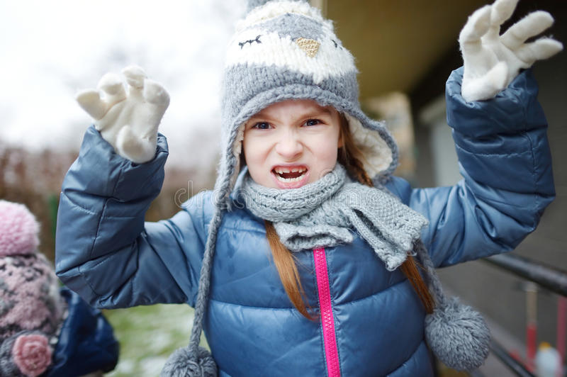 Adorable little girl making funny faces outdoors. Adorable little girl wearing winter hat making funny faces on beautiful winter day outdoors stock image