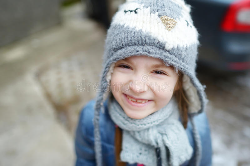 Adorable little girl making funny faces outdoors. Adorable little girl wearing winter hat making funny faces on beautiful winter day outdoors royalty free stock photo