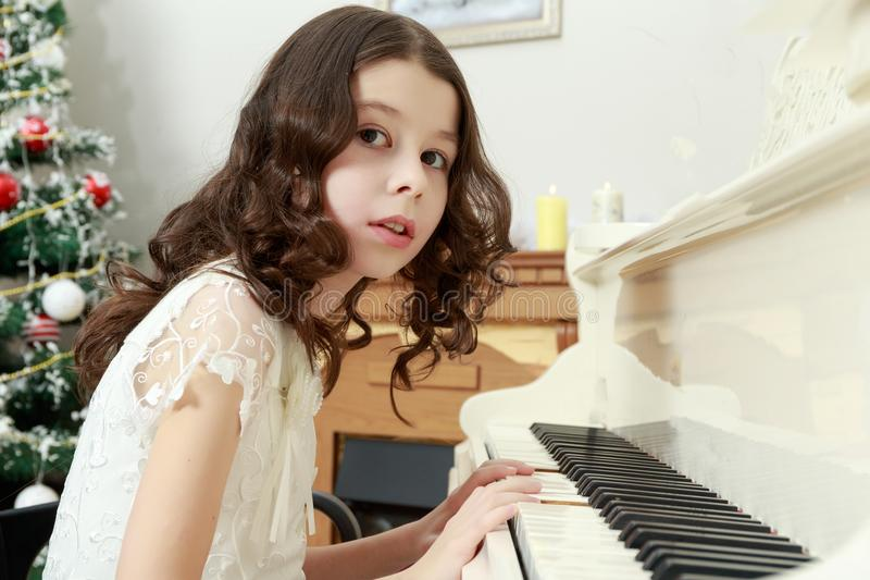 Beautiful girl in a white dress sitting at the piano. royalty free stock photography
