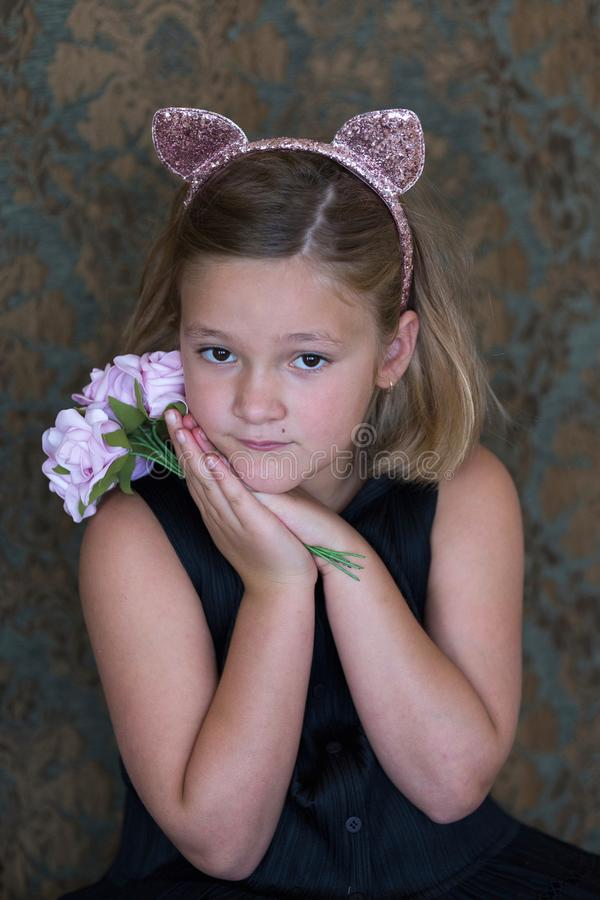 Little girl in pink cat hairband and black sleeveless dress holding a bouquet royalty free stock images