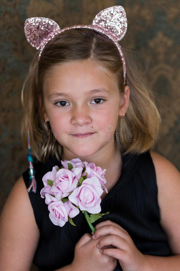 Adorable little girl in pink cat hairband and black sleeveless dress holding a bouquet stock photos